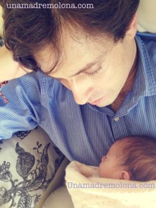 El padre victorioso, disfruta de su pequeña cría tras superar con éxito el cólico no divertido